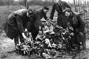 Servicemen hunt through the crumpled remains of the Heinkel which crashed and exploded in Beach Road in February 1941.