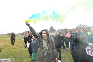 A woman lets off blue and yellow flares