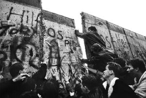 BERLIN, GERMANY - NOVEMBER 1989: The first section of the Berlin Wall is pushed down by the hands of crowds of determined people on the morning of November 10th 1989. Picture by Tom Stoddart.
