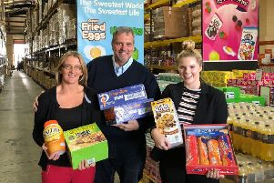 Andy Needham of Approved Food hands over donations to Lisa Bottomley and Ellena Roberts from the Town Foundation.