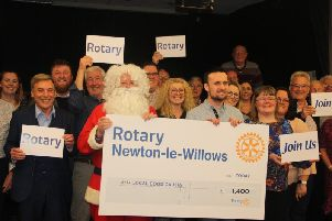 Santa is pictured giving 1,400 to the representatives of the local community groups who helped him last year