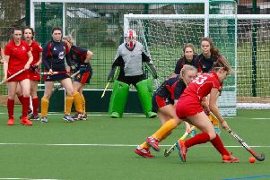 Garstang Hockey Club's Holly Hunter in possession as Rebecca Worthington and Summer Muirhead wait in front of goal