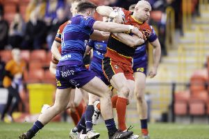 Dewsbury's Adam Ryder is halted by the Swinton defenceduring Sunday's 38-24 victory. Picture: Allan McKenzie