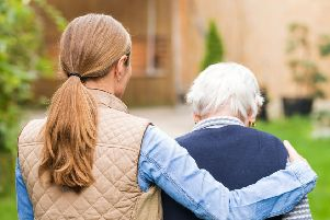 A young carer walking with an elderly woman.