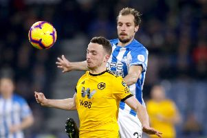 Fighting for his place: Huddersfield Town's Jon Gorenc Stankovic with Wolverhampton Wanderers' Diogo Jota.