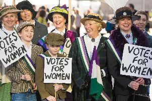 Participants dressed in suffragette period costume take part in CARE International's Walk in Her Shoes march in central London, to mark International Women's Day.