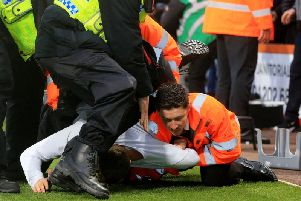 A Newcastle United fan is restrained by stewards and police after invading the pitch during the Premier League match at the Vitality Stadium, Bournemouth. Pic: Mark Kerton/PA Wire.