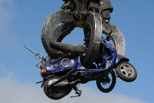 A seized off-road motorbike being crushed.