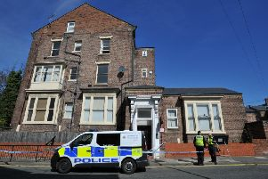 Police outside the house following the woman's fall from a window on Friday.
