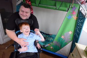 Benjamin Edmundson-Brown, 12 in his new house extension bedroom to fit his needs with step father Peter Kell.