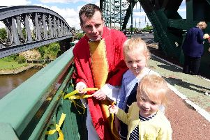 Fr Marc Lyden-Smith with Nancy (7) and Harriett (4) Corr, tying yellow ribbons to Wearmouth Bridge to raise awareness of Cystic Fibrosis.