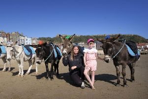 Donkey beach worker Lucy Butterfield with regular donkey visitor Lily Baker on South Bay. PIC: Richard Ponter