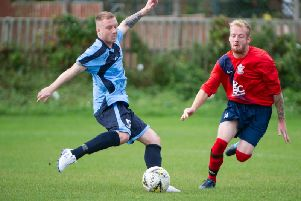 Filey Town, blue kit, battle it out in their 1-1 home draw against Ayton