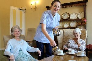 Chloe Baxter serves morning coffee to two Combe Hay residents.