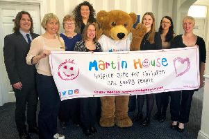 Pinkney Grunwells staff (l-r) Michael Johnson, Julia Jackson, Debbie Gibson, Alison Jeffels (back), Tracy Murray, Rebecca Crosier, Christina Severn and Victoria Moss with Martin House mascot Marty Bear.