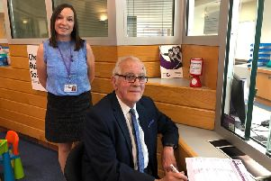 Chorley Building Societys Amy Egginton, watches as Rosemere Cancer Foundation patron Dennis Benson signs up to the new affinity account