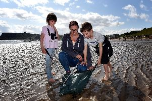 Connie and Max Ireland with Mum Hayley at work on North Bay. PIC: Richard Ponter