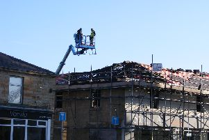 Workers survey the damage to the roof at the burned out building in Burnley Road, Padiham.