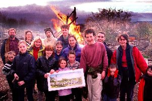 A community  bonfire was lit at Heeley City Farm on the site of what will be the new stables to replace the ones gutted by arsonists. Seen are farm workers and supporters with a picture of the new buildings, with the bonfire behind them, March 17, 2000