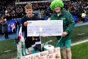 William Hunter hands over his cheque to John Burkhill on the pitch at Hillsborough.