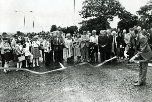 Coun Norman West, Chairman of the Highways Committee, cuts the tape to officially open the new Norton bypass, watched by councillors, officials and members of the public, June 28, 1982