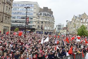 Sheffield United fans celebrate their promotion to the Premier League at Sheffield Town Hall.