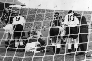 Players gather round the goal mouth as Manchester City's goalie, Bert Trautmann, receives medical attention to his neck, during the FA cup final against Birmingham City at Wembley