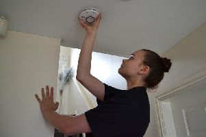 Merseyside Fire and Rescue Service apprentice Jessica Lewis fitting a smoke alarm.