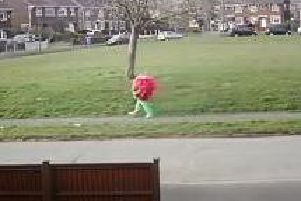 A giant strawberry walking down the street in Kirk Hallam.