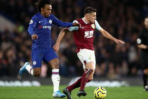 Burnley midfielder Ashley Westwood holds of Chelsea winger Willian at Stamford Bridge