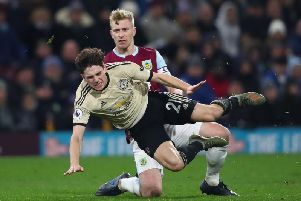 Clarets skipper Ben Mee challenges Manchester United's Daniel James at Old Trafford
