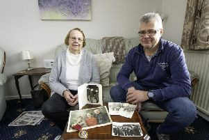 Beverley Greenwood with Mark Greenwood and the photos of her father-in-law and Mytholmroyd firefighter Clifford Greenwood. Photo by Allen McKenzie.
