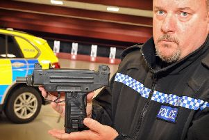 Sergeant Pete Moss with a small machine gun handed in, in the nationwide firearms surrender program 2018