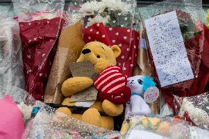Soft toys and floral tributes placed outside the house on Second Avenue at Rothwell after the fatal fire.