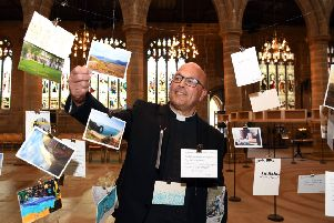 The Very Revd Simon Cowling Dean of Wakefield, with the favourite Places Favourite Journeys postcards hanging at Wakefield Cathedral.