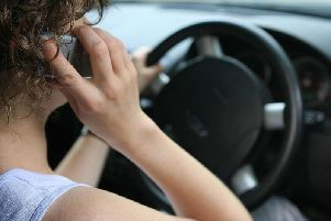 File photo of a woman using a mobile phone while driving as fiercer fines are failing to stop motorists using hand-held mobile phones while driving, figures show