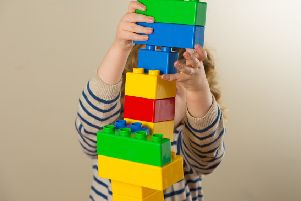 A preschool age child plays with plastic building blocks.