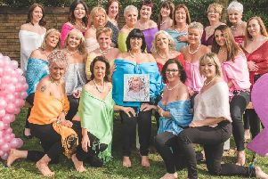 The 22 ladies, including Lynne Aspey (centre holding a picture of sister Josie), who took part in a Calendar Girls photoshoot