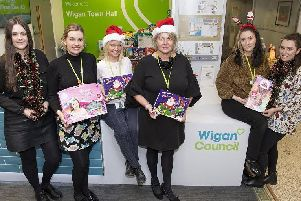 Council staff, with CEO Alison McKenzie-Folan far right, backing the Toy Appeal collecting gifts for disadvantaged youngsters, and below Rachael Speakman and Kirsty Waite at Wigan Investment Centre, with the Christmas hamper collection for The Brick charity
