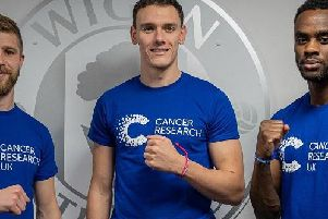Wigan Athletic players Michael Jacobs, Kal Naismith and Gavin Massey wear Cancer Research UK Unity Bands ahead of World Cancer Day on February 4