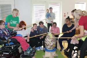 Nick Edwards and his daughter Penelope (centre back) with staff and children at Rainbow House breaking the giant chocolate egg