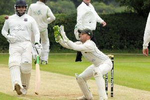 Hucknall wicket keeper Tom Walters receives the ball from the field ahead of the in-coming Bilal Shafayat.