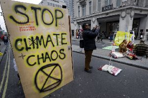 Writing on the side of a temporary toilet set up as the road is blocked during a climate protest at Oxford Circus in London, Tuesday, April 16, 2019. The group Extinction Rebellion is organizing a week of civil disobedience against what it says is the failure to tackle the causes of climate change. (AP Photo/Kirsty Wigglesworth)