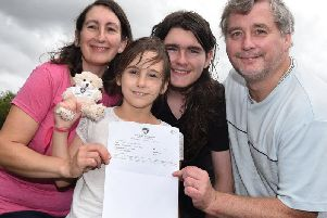 Eight-year-old Ellie Barnes celebrates gaining the top grade, nine, in her maths GCSE exam, pictured with proud family, mum Angela, brother Thomas,12, and dad Simon, right