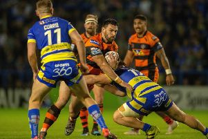 Matt Cook is held by Joe Philbin. during last week's eliminatior between Warrington Wolves and Castleford Tigers.' Picture: Bruce Rollinson