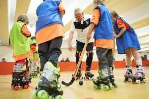 Keith Whitton, chairman of Sheffield Wildcats Rink Hockey Club, coaching some of the youngsters.
