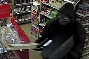 One of the robbers was wearing a Halloween mask and wielding a piece of wood.