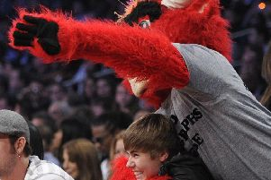 Appealing to the masses: The Chicago Bulls basketball mascot jokes around with Justin Bieber.
