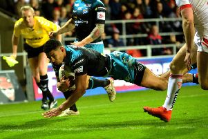Kallum Watkins dives over for the Rhinos' first try at St Helens.