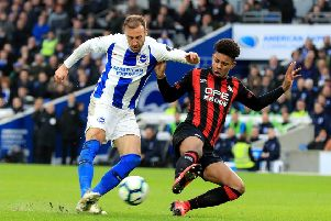 Brighton & Hove Albion's Glenn Murray (left) has a shot defended by Huddersfield Town's Juninho Bacuna (right).